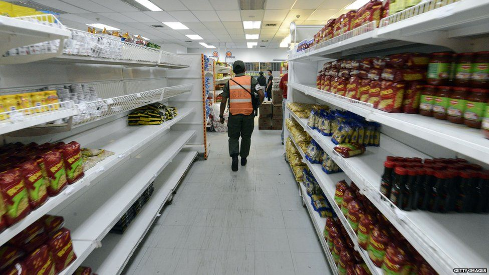 Member of the national guard patrolling a supermarket aisle with many empty shelves
