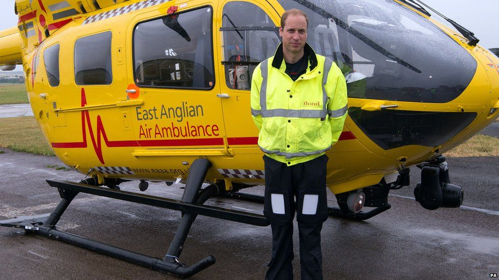 Prince William in front of an East Anglian Air Ambulance helicopter
