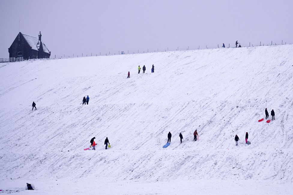 People sledge down a hillside at Butterley Reservoir in Marsden, West Yorkshire, on 14 January 2021