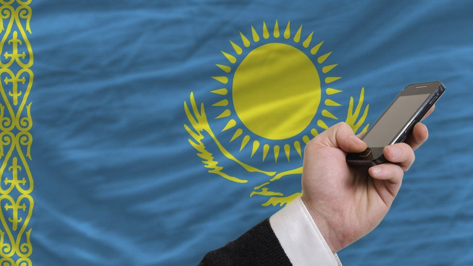 A phone in front of the Kazakhstan flag
