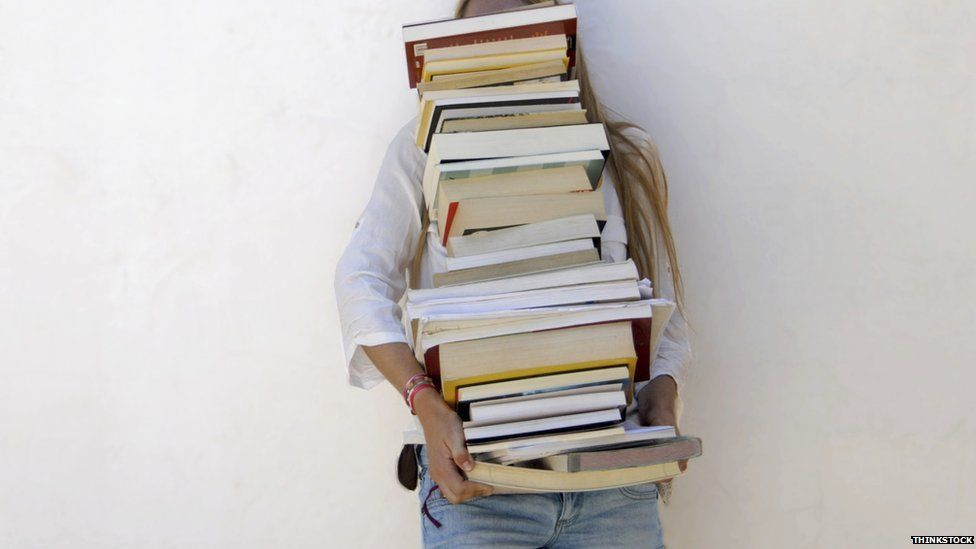 Girl carrying a big stack of books