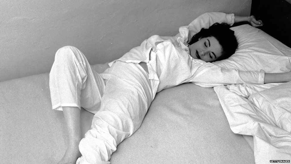 Black and white photo of a woman in pyjamas stretching on a bed