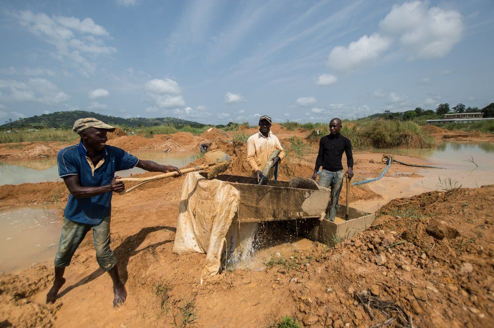 The men shovel dirt into a trough and then wash it with water