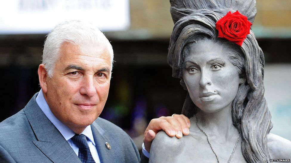 Mitch Winehouse posing with the statue of his daughter Amy which was unveiled in 2014