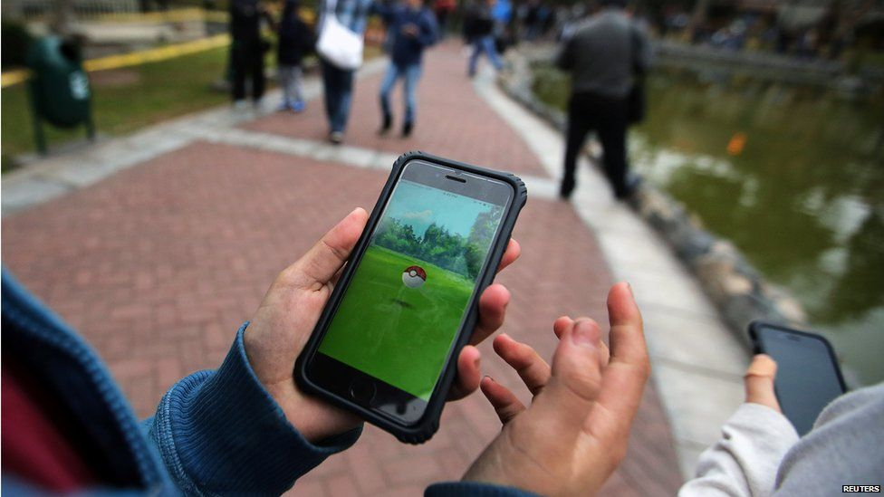 People playing Pokemon Go in a park