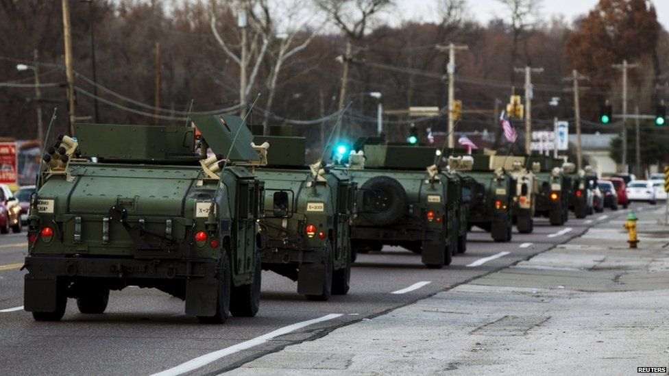 National Guard vehicles drive down W. Florissant Ave. which had been heavily damaged during protests that erupted in reaction to the grand jury verdict in the Michael Brown shooting near Ferguson, Missouri