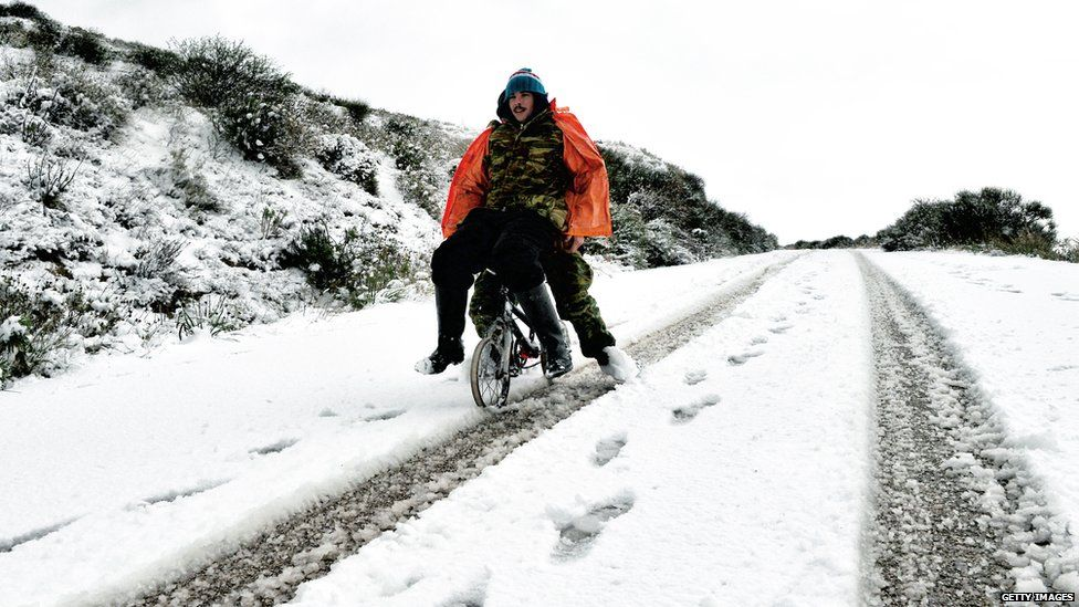Two people on a bike going down a snowy road