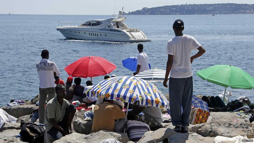 People sitting under umbrellas looking at a boat