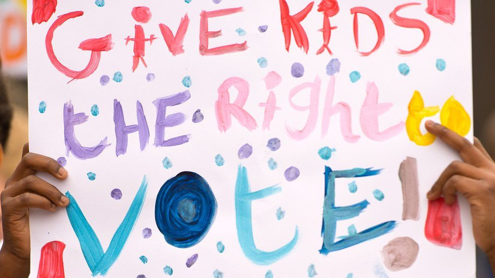 "A placard saying ""give kids the right to vote"""