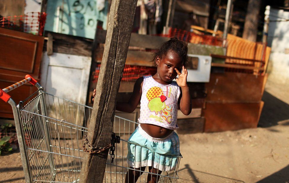 A young girl stands in a shopping cart in the poverty ridden City of God favela, or slum, on December 2, 2009 in Rio de Janeiro