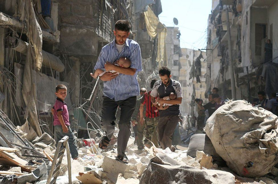 Syrian men carrying babies make their way through the rubble of destroyed buildings following a reported air strike on the rebel-held Salihin neighbourhood of the northern city of Aleppo on 11 September 2016.