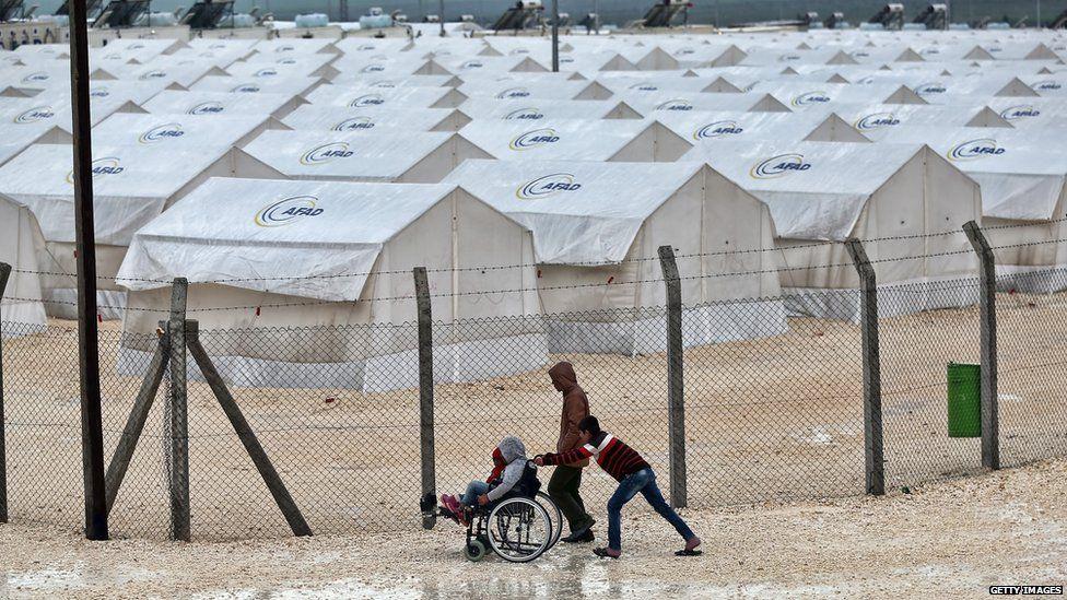 A boy pushes a wheelchair in Suruc refugee camp