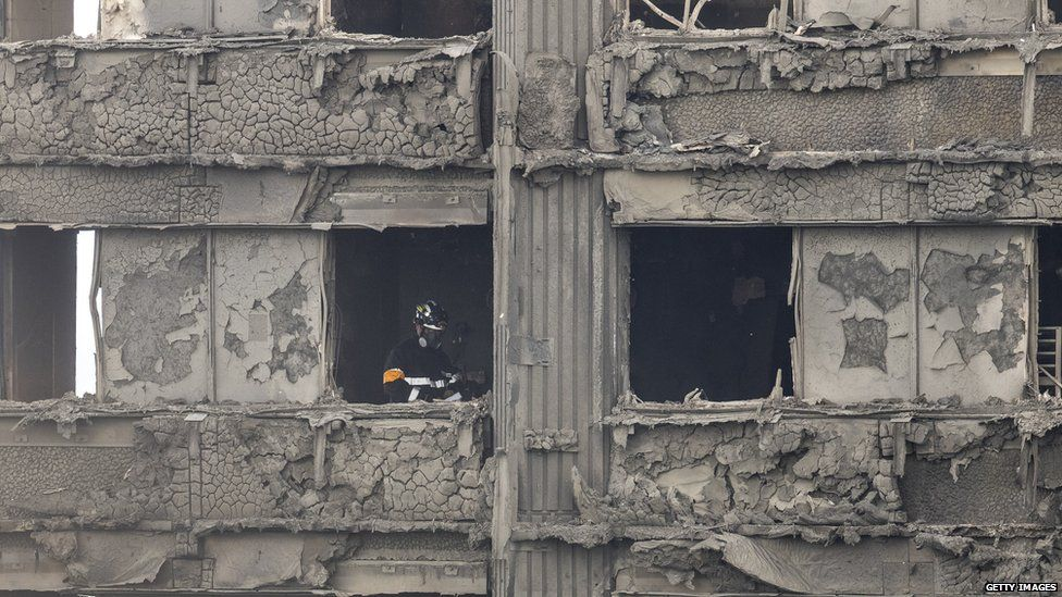 A firefighter works through the rubble of Grenfell Tower