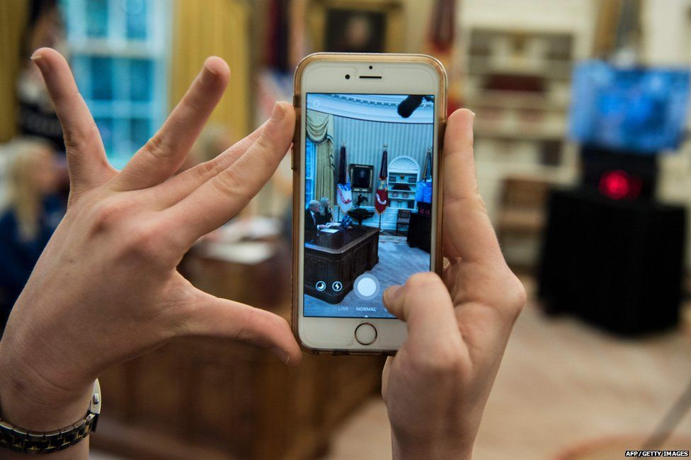 A White House staff member recording the conversation on their phone