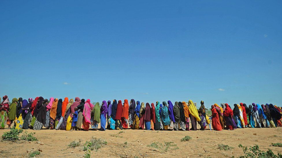 Displaced Somalis queue for aid after flash floods.