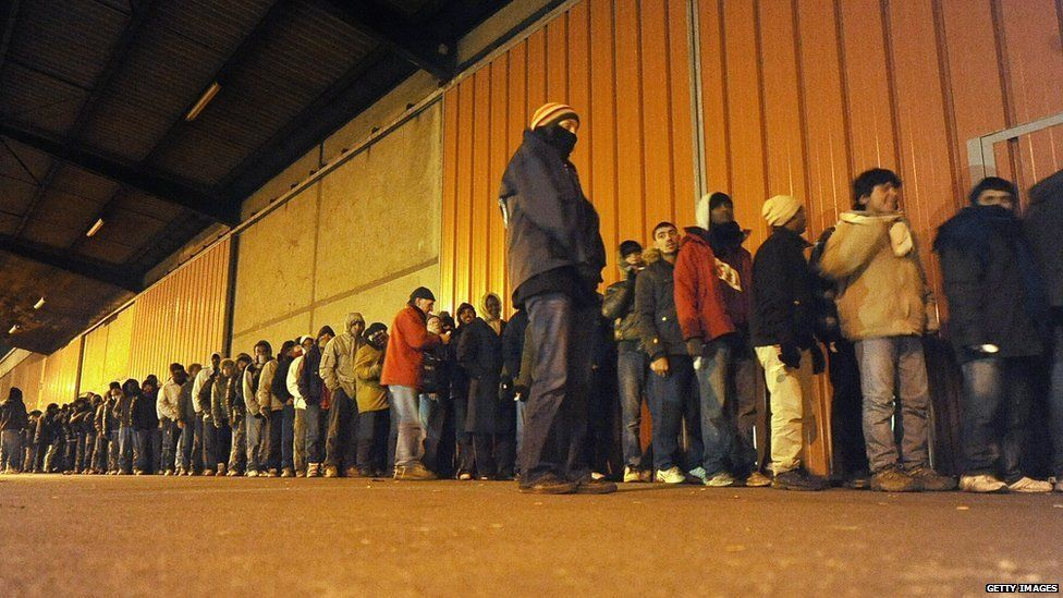 A long queue of refugees waiting for dinner