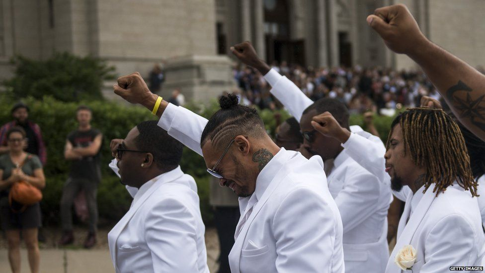 Pallbearers with their fists raised at the funeral of Philando Castile