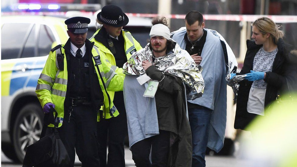 One of the injured is helped by police