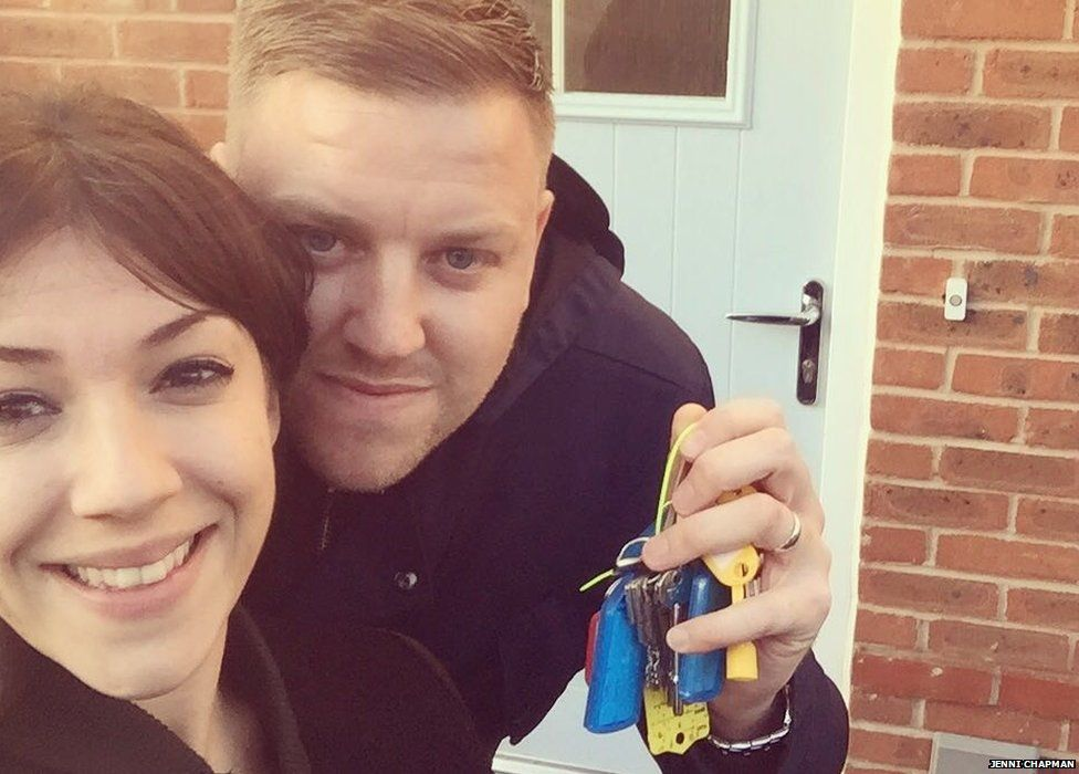 Jenni with her husband with their house keys in front of their new home