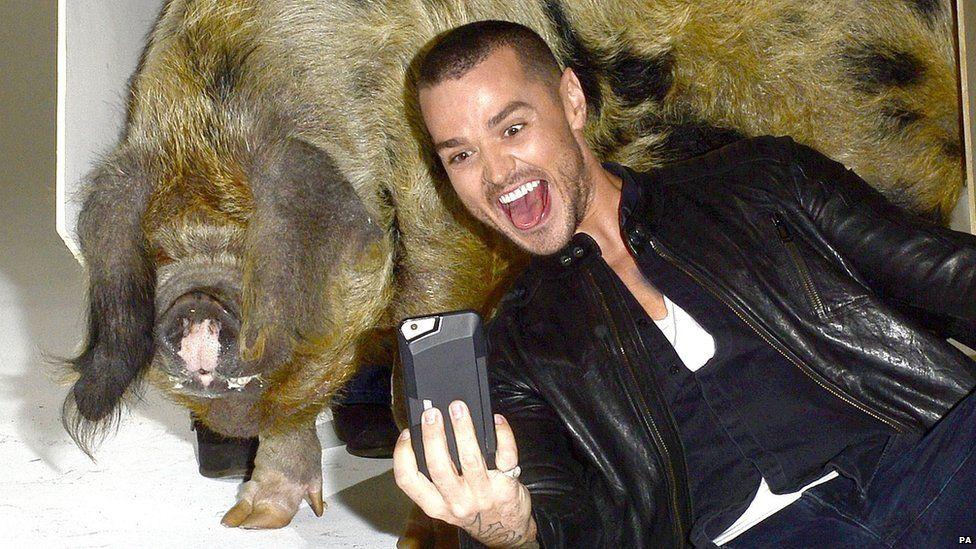 Matt Willis taking a selfie with a pig