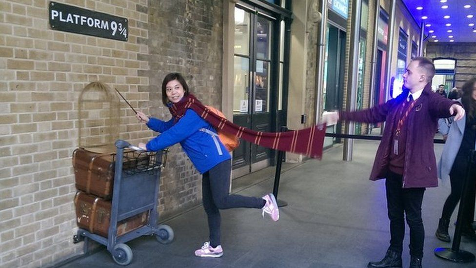 People having their picture taken at Platform 9 and 3/4s