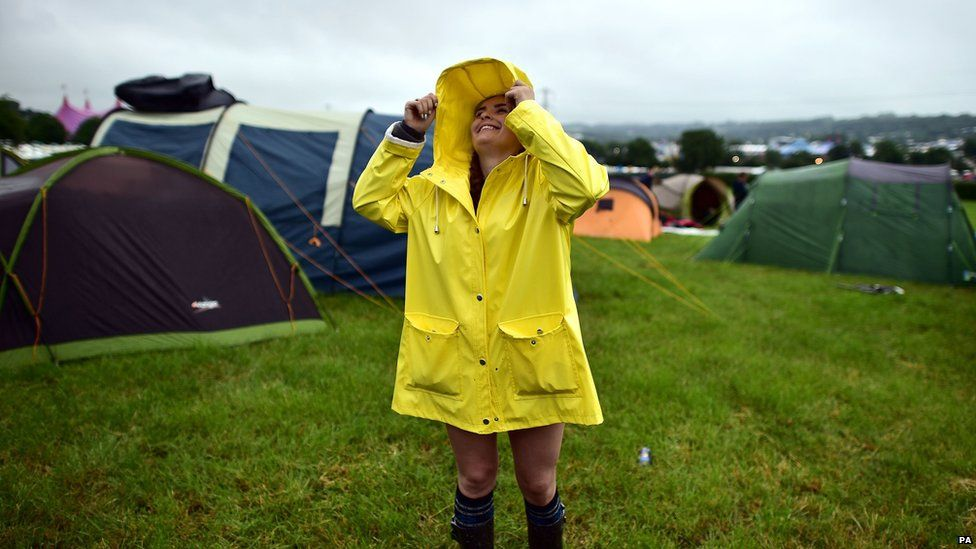 Girl wearing a mac by some tents