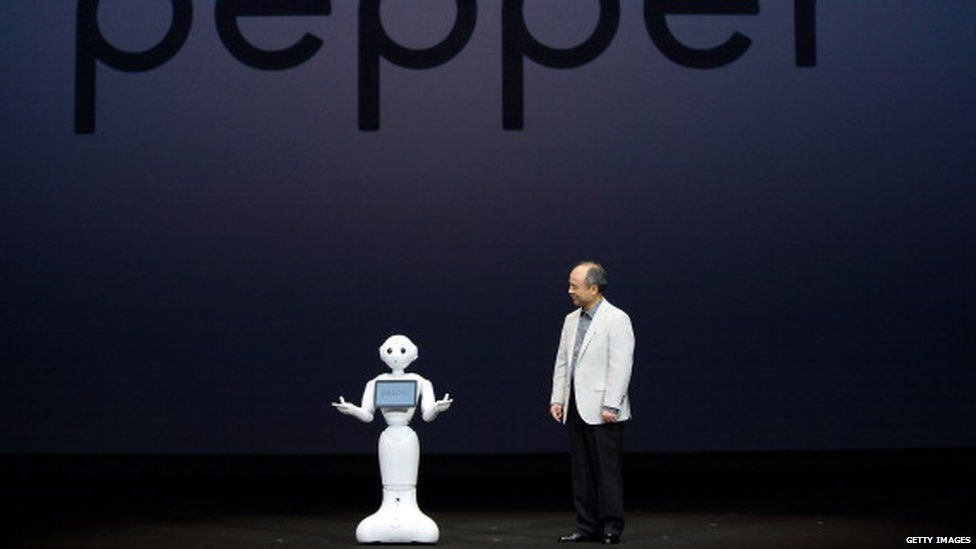 Masayoshi Son (R), president of Japan's mobile carrier SoftBank, introduces the humanoid robot 'Pepper'