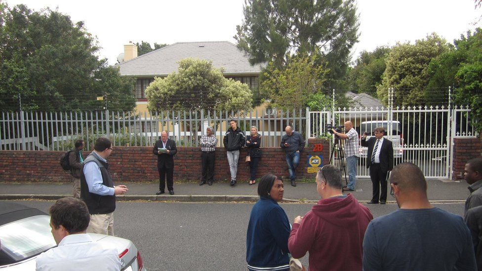 Bidders stand outside a Zimbabwe government-owned house in Cape Town