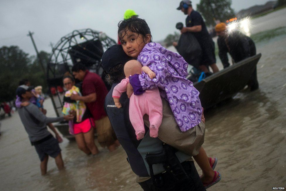 A girl is rescued from flood waters