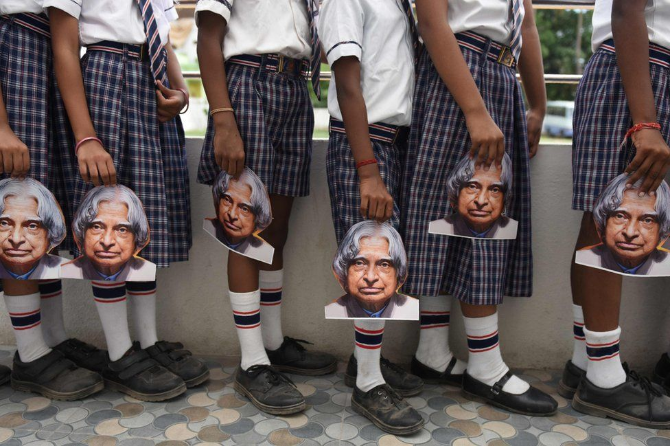Indian schoolchildren hold masks bearing the image of former Indian president AP Kalam at a school in Chennai