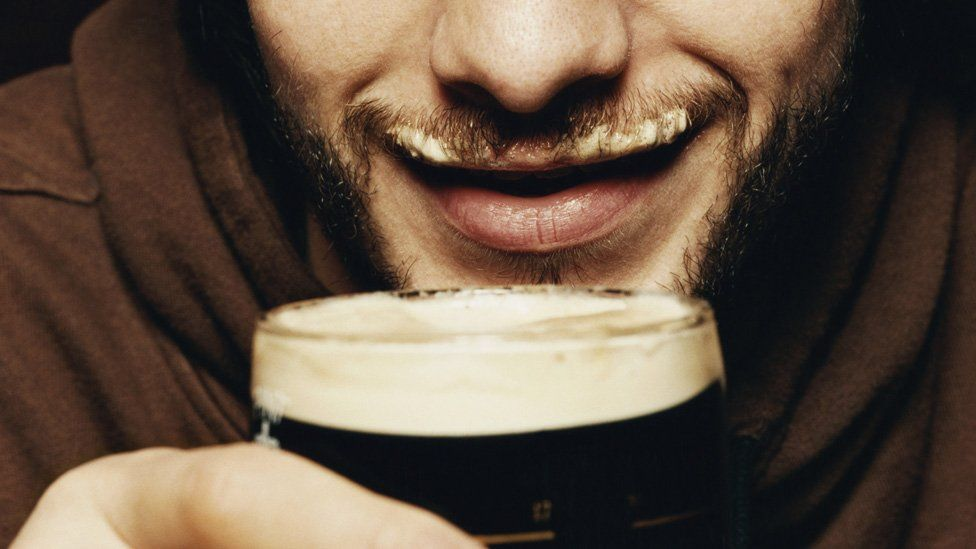 Man drinking pint of Guinness