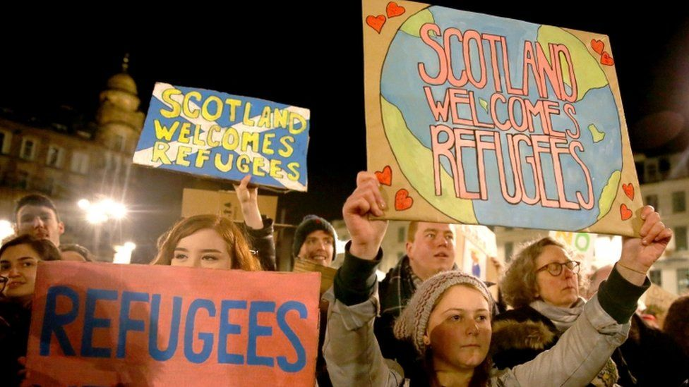 Signs saying Scotland supports refugees