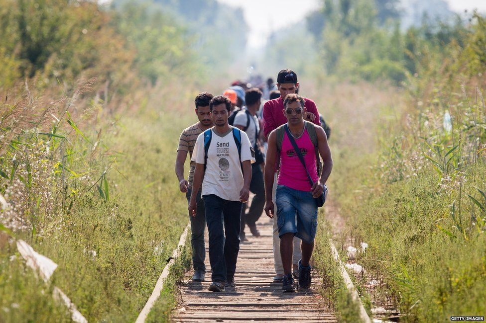 A group of migrants walk to the border with Hungary in the village of Horgos in Kanjiza, Serbia