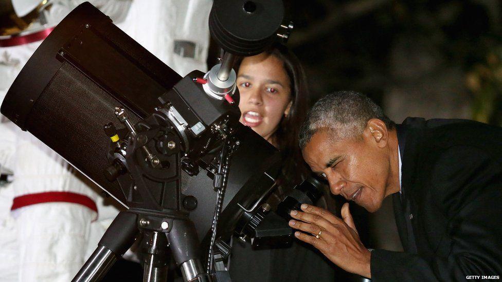Barack Obama looks in a telescope