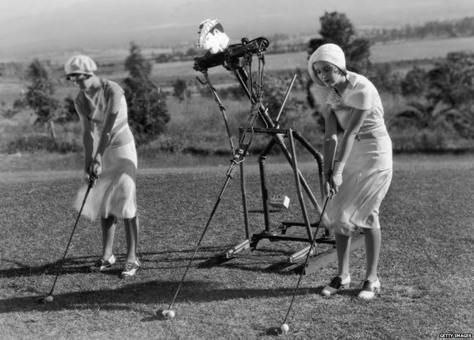 Two golfers use a golf robot trainer to help with their golf swing.
