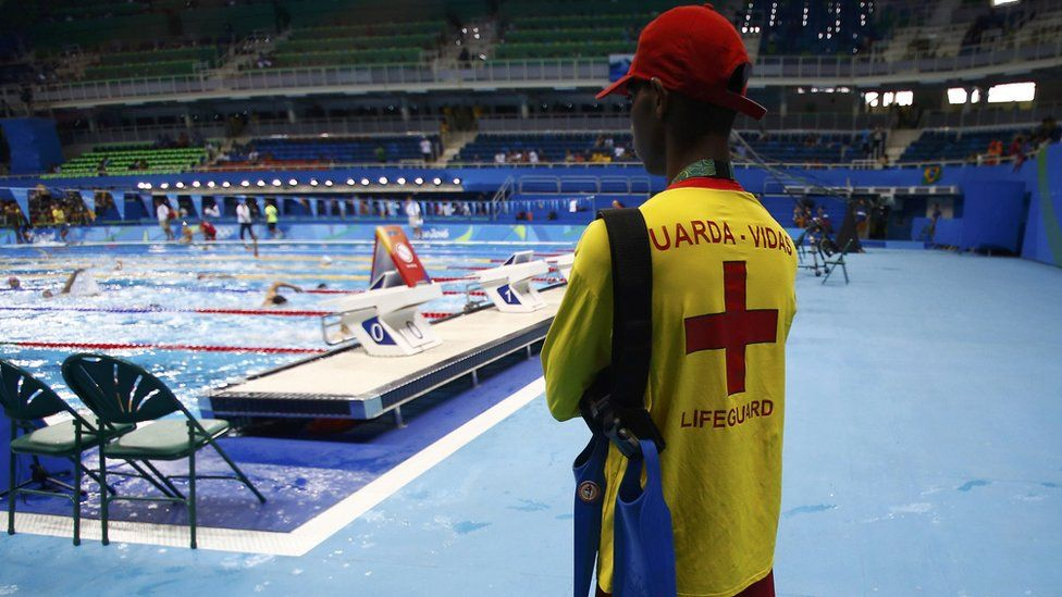 A lifeguard watches over swimmers in the Olympic pool