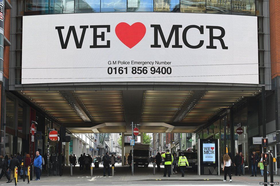 "A sign saying ""We love Manchester"" displayed above a street in Manchester"