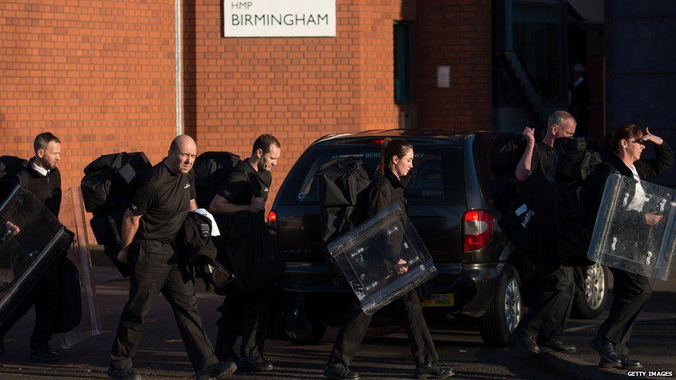 Prison staff carrying riot shields leave HMP Birmingham in Winson Green, Birmingham