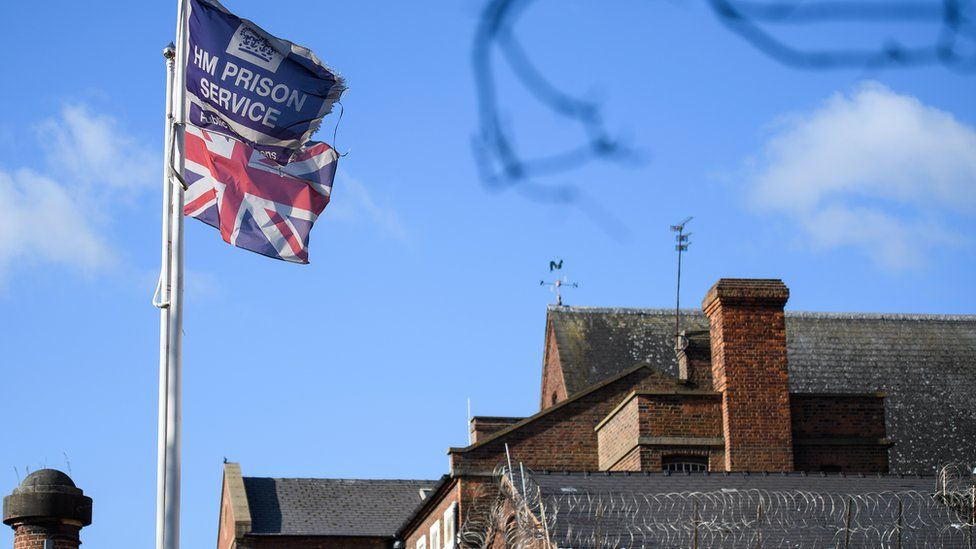 A union jack and a HM Prison service flag flying at a prison