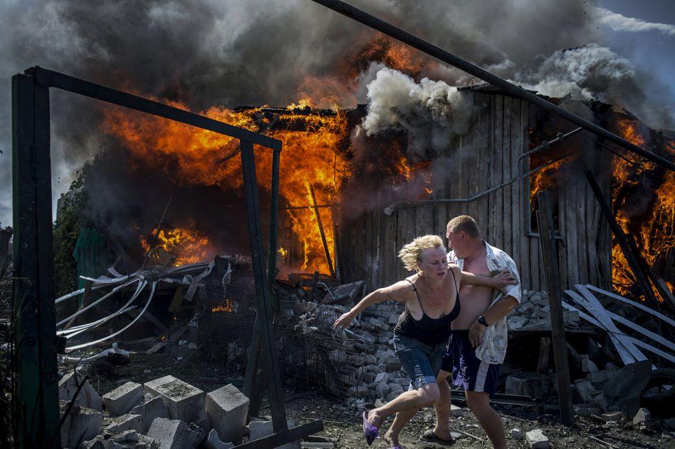 một cặp vợ chồng chạy khỏi căn nhà đang bốc cháy do không tập tại làng Luhanskaya, Ukraine.