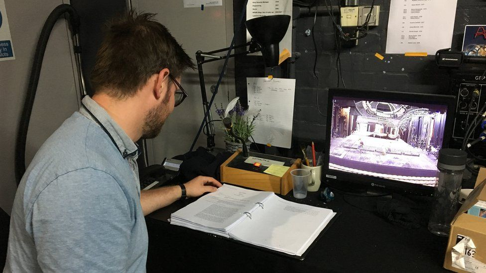 Shane watches the actors on a monitor backstage and reads the script to get his cues