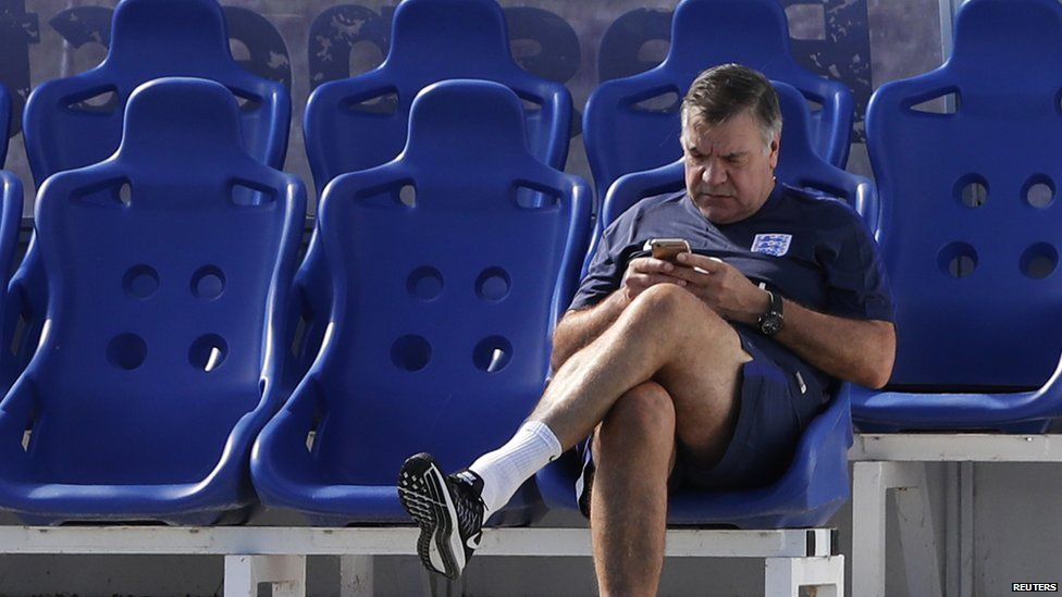 Sam Allardyce looking at his phone