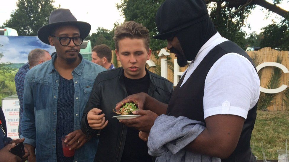 Luke Thomas with Gregory Porter holding some food