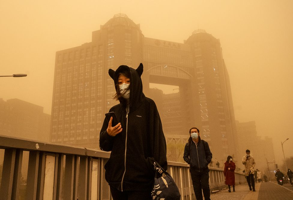 People wear protective masks as they walk along a street during a sandstorm on 15 March 2021 in Beijing, China