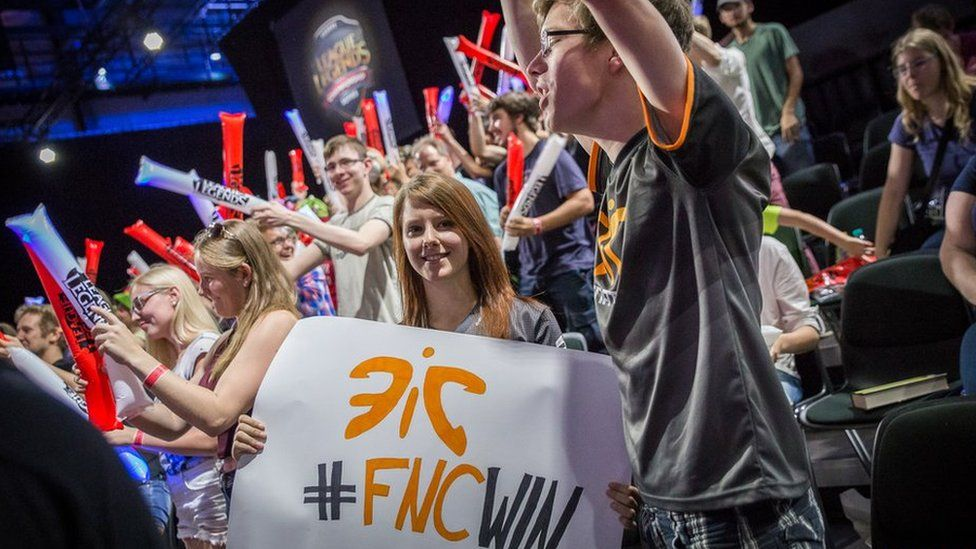 Fans hold up team banners at a League of Legends tournament