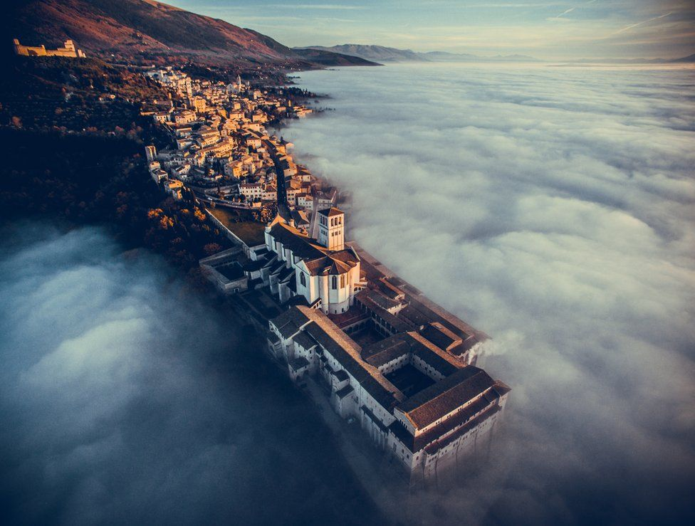 Basilica of Saint Francis of Assisi at sunset immersed in fog