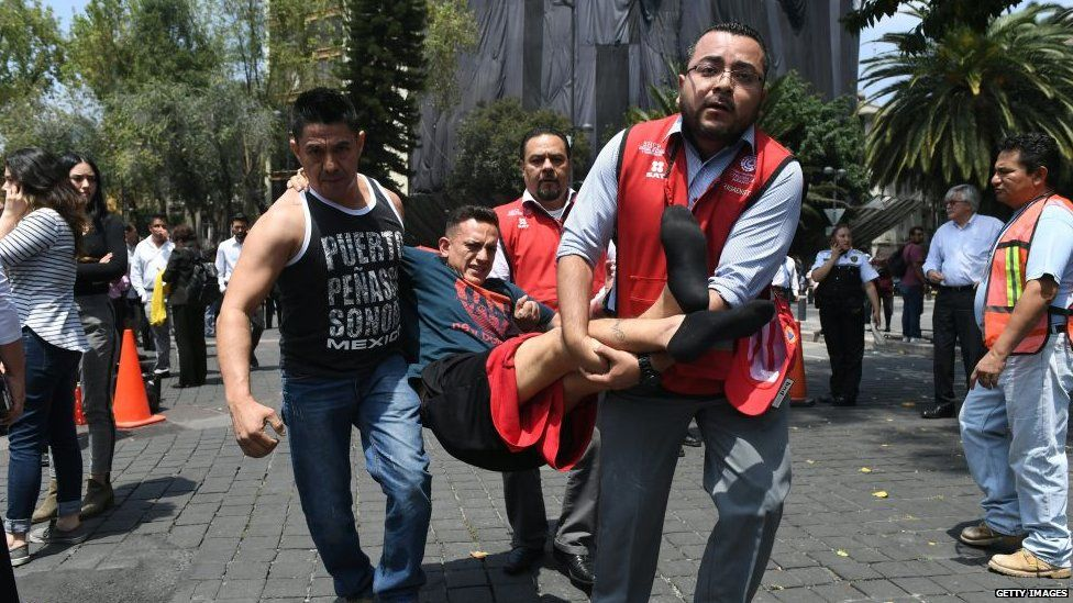 A rescued person is carried by two other people