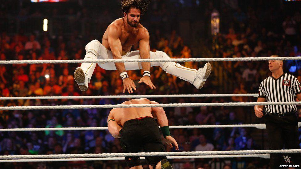 Seth Rollins jumping over John Cena