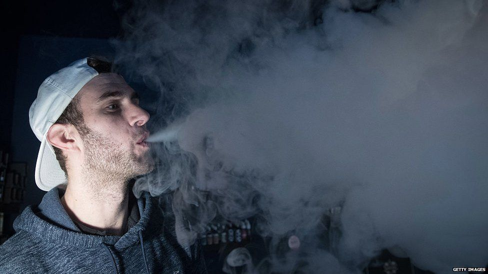 A man blowing smoke against a black background
