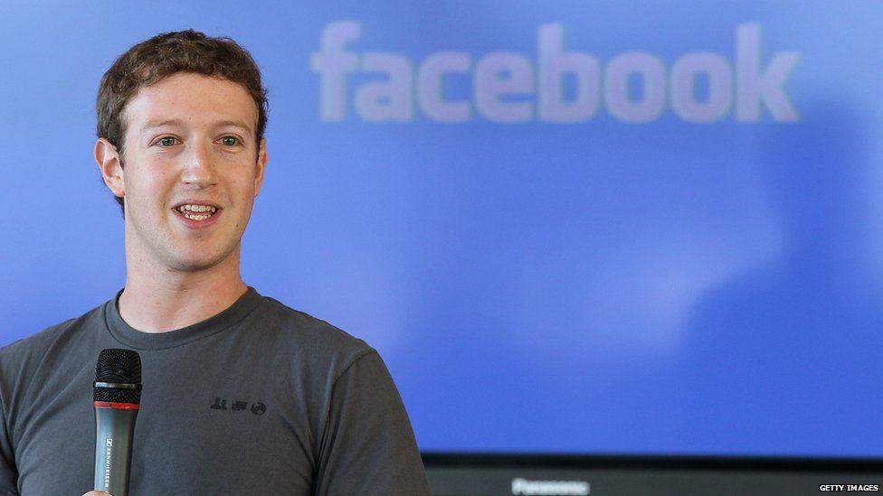 Facebook CEO & founder Mark Zuckerberg in front of the Facebook logo
